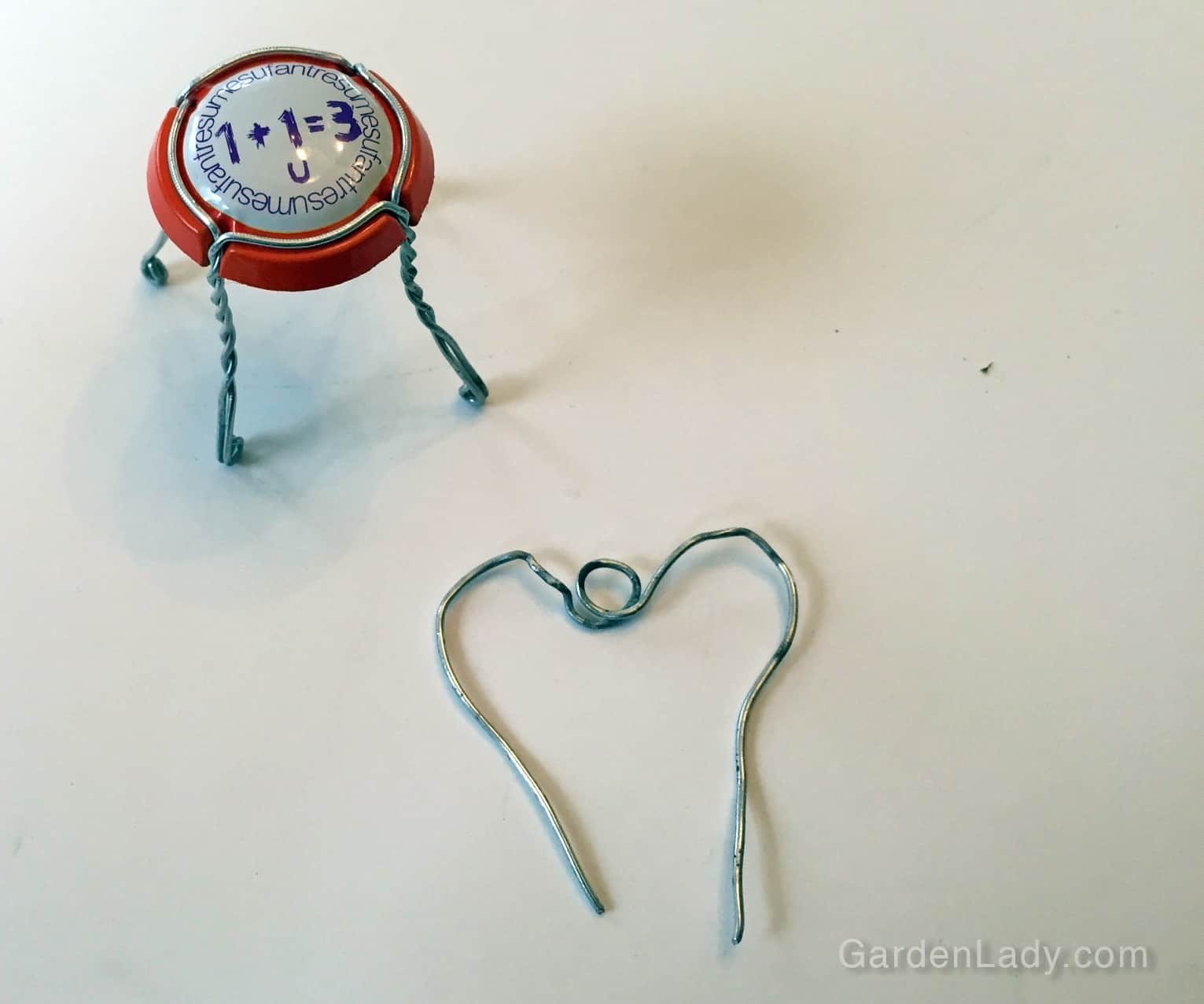 Find the middle of the wire - decide if you want to bend it into a round top, have a circle or other crimping, or make it into a heart shape.