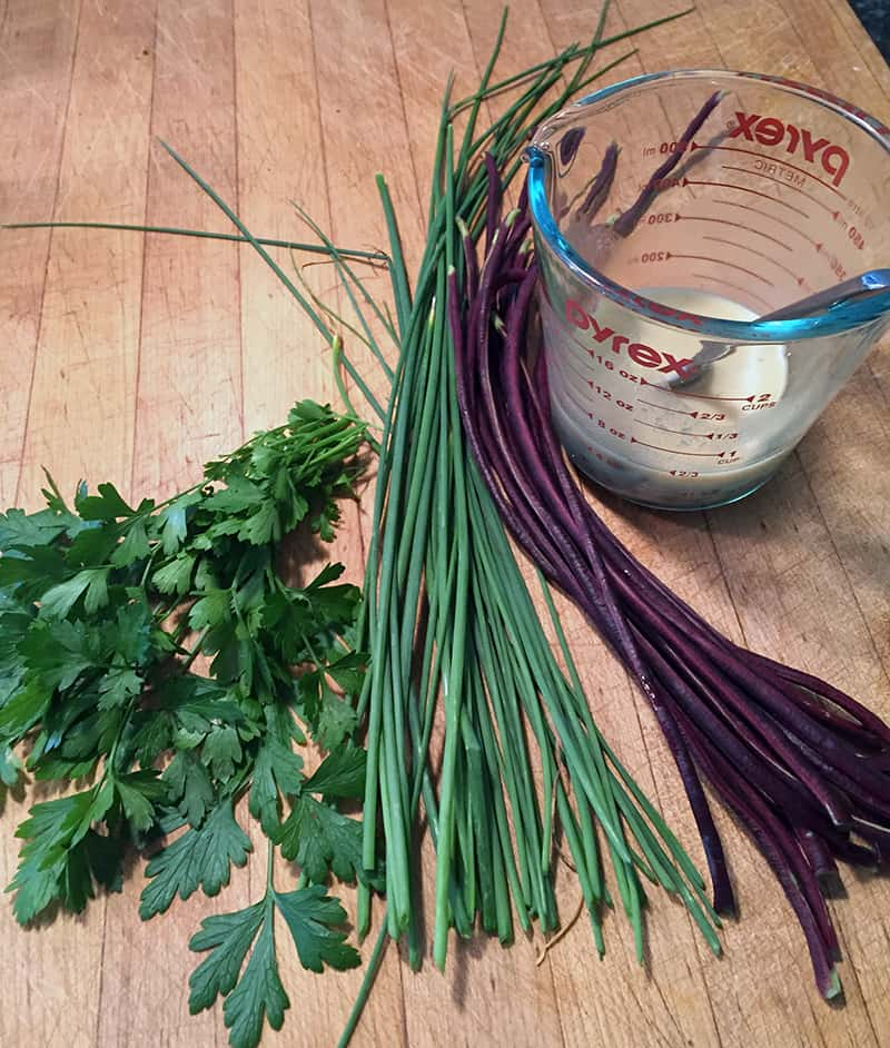 chives on a cutting board with red noodle beans and cilantro, ready to make into a stir-fry