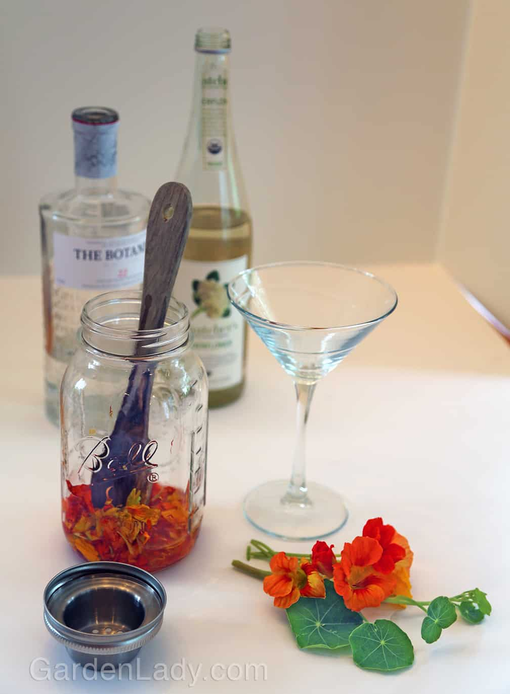 Muddle the flowers by smashing them with a wooden spoon, then add the liquids.